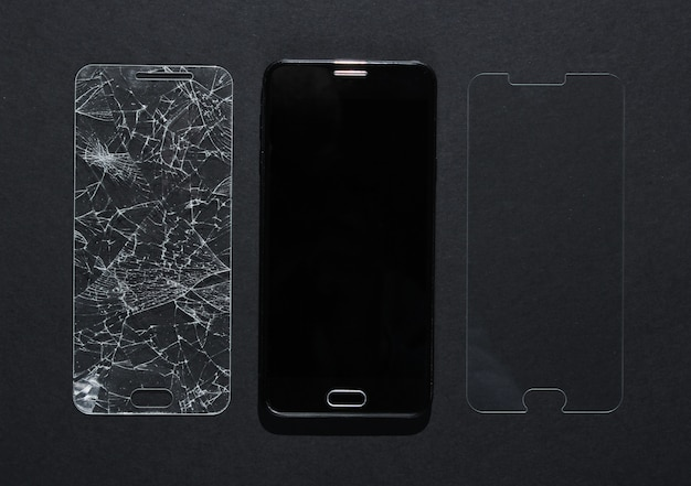 Smartfon ze stłuczonym i nowym szkłem ochronnym na czarnym stole. widok z góry