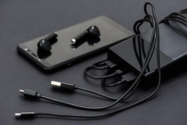 Smartfon, zestaw słuchawkowy, power bank z kablami do ładowania