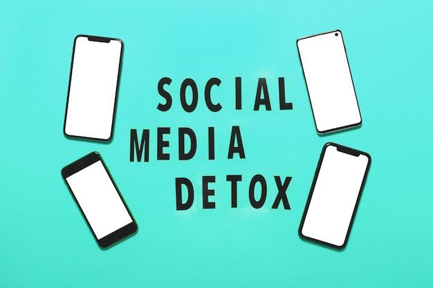 Smartfony i słowa social media detoks na lightbox na miętowym tle. uzależnienie od mediów społecznościowych. koncepcja unlpug, przerwa technologiczna. widok z góry, płaski układ