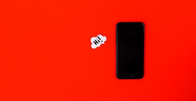Smartfony z papierową mową gulgoczą na czerwonym tle. koncepcja komunikacji. widok z góry. skopiuj miejsce skład papieru z tekstem cześć