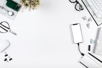 Smartphone ładuje na obszarze roboczym z biurowymi narzędziami