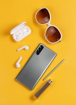 Smartphone, bezprzewodowe słuchawki, okulary przeciwsłoneczne i szminka na żółtym tle widok z góry