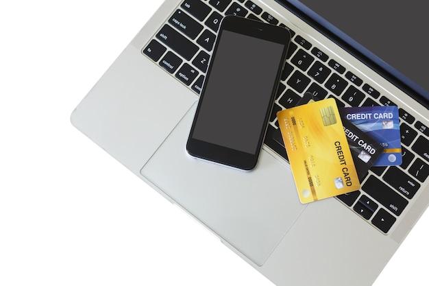 Smartphone czarny ekran z karty kredytowej na laptopie na białym tle, ścieżka przycinająca. sfinansuj płatność online.