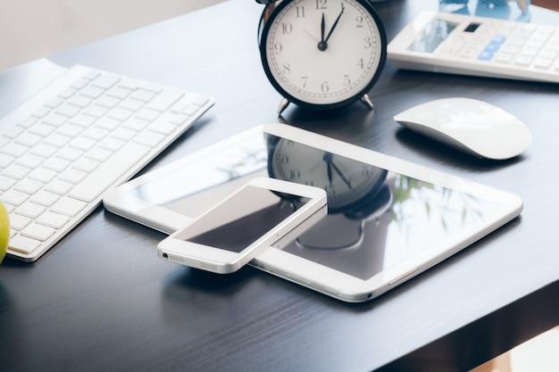Smartphone i komputerowa klawiatura na biuro stołu zakończeniu up