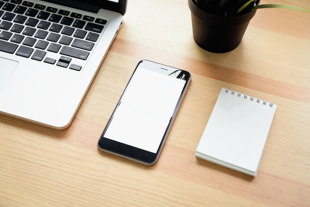 Smartphone i laptop na stole w pokoju biurowym, do montażu wyświetlacza graficznego.