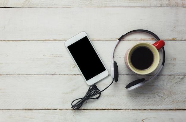 Smartphone i słuchawki z widokiem na góry z filiżanką kawy