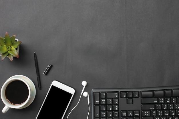 Smartphone, klawiatura, notatnik, filiżanka kawy, długopis i materiały na czarnym biurku.
