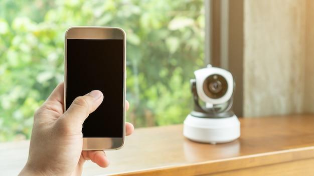 Smartphone łączy się z kamerą bezpieczeństwa ip na drewnianym stole.