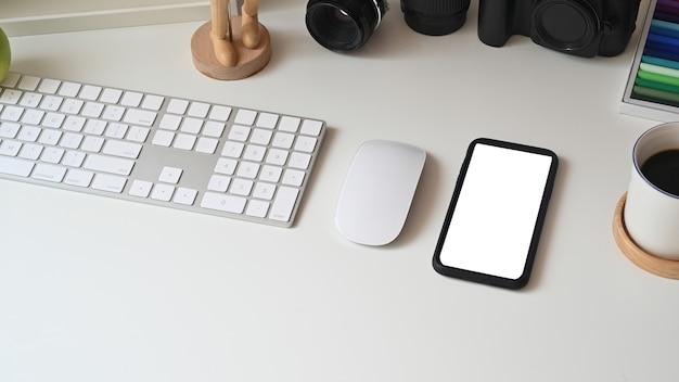 Smartphone na białym tle wyświetlacz na kreatywnym stole z aparatem i sprzętem komputerowym.