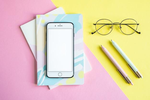 Smartphone na dwóch notebookach na różowym tle i okulary i długopisy na żółtym tle