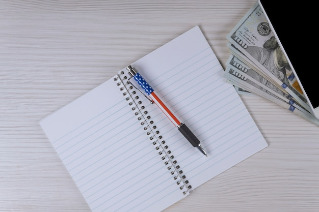 Smartphone, notatnik i pióro na sto dolarowych rachunkach.