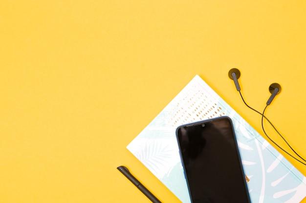 Smartphone Notebook Słuchawki I Długopis Na żółtym Tle Premium Zdjęcia