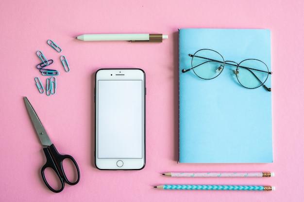 Smartphone, nożyczki, notatnik, okulary, klipy, długopis i ołówki na różowym tle