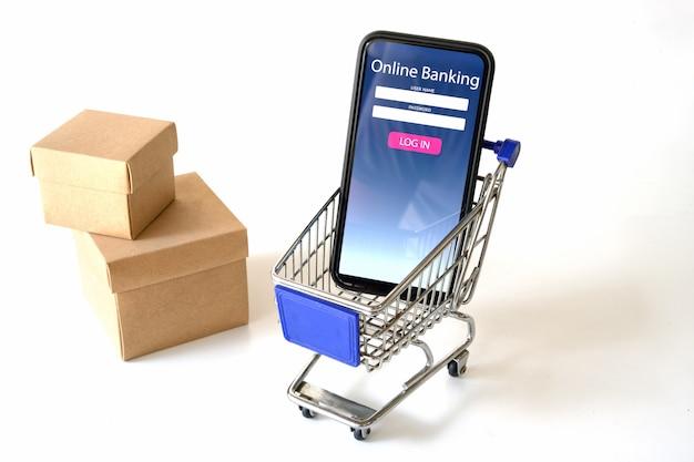 Smartphone pokazuje online płatniczą aplikację na makieta wózek na zakupy na bielu.