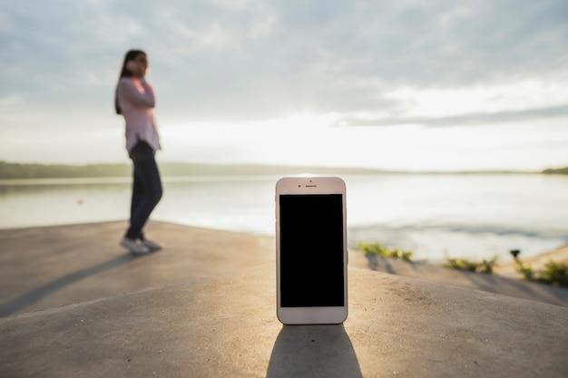 Smartphone przed kobietą opowiada na telefon komórkowy pozyci blisko jeziora