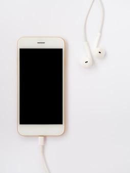 Smartphone, słuchawki douszne i kabel do ładowania na białym