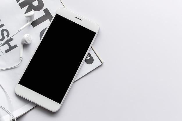 Smartphone, słuchawki i magazyn na białym stole z nad światłem w tle