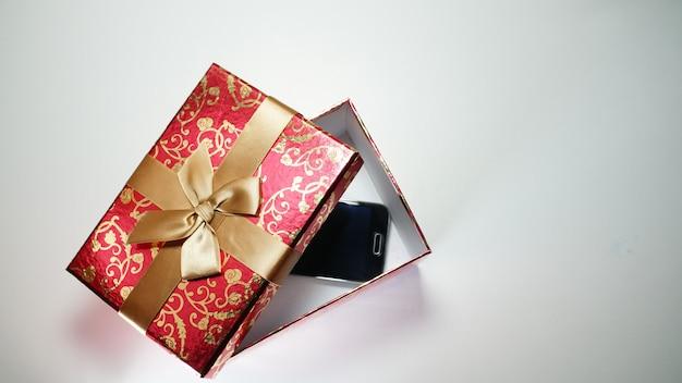 Smartphone w czerwonym pudełku na białej przestrzeni
