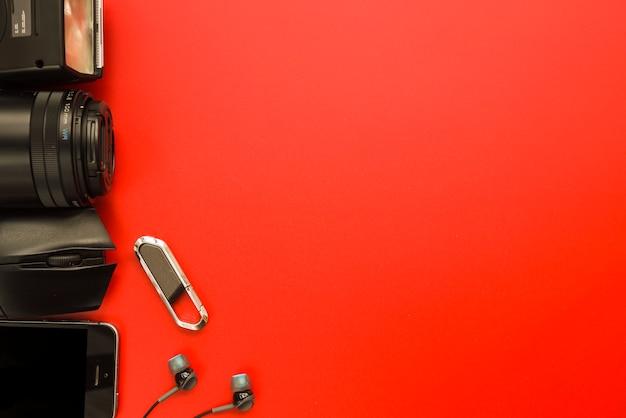 Smartphone w pobliżu sprzętu fotograficznego, myszy komputerowej, pamięci flash i słuchawek
