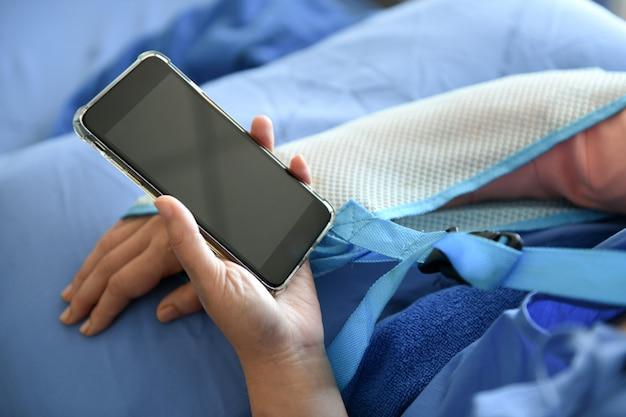 Smartphone w ręce pacjenta, on używa połączenia wideo.
