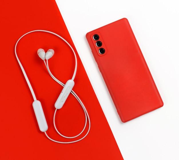 Smartphone z czerwoną okładką i białymi bezprzewodowymi słuchawkami widok z góry na czerwonym i białym tle