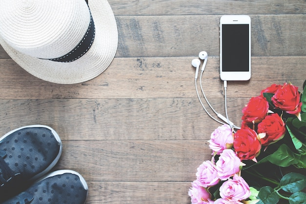 Smartphone z czerwonym i ró? owe ró? e, kapelusz i tenisówka na drewnianej pod? odze z kopi? miejsca