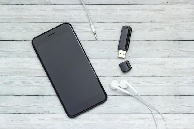 Smartphone z hełmofonami i błysk przejażdżką na drewnianym tle, muzyczny magazynu pojęcie