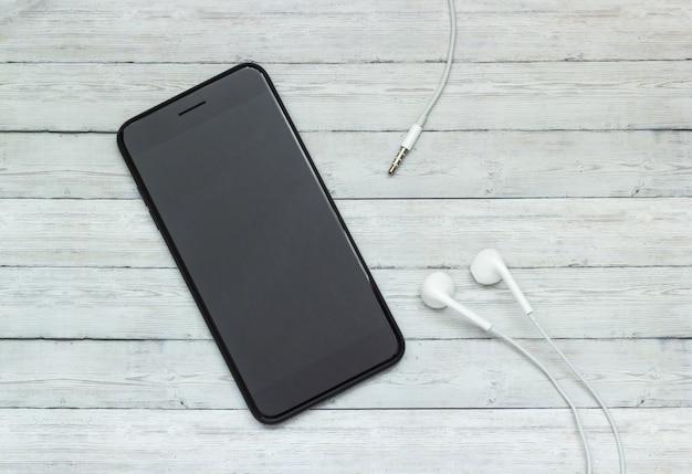 Smartphone z hełmofonami na drewnianym tle