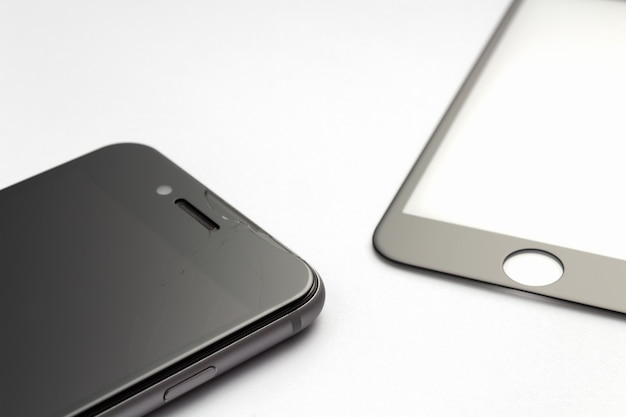 Smartphone z krakingowym ochronnym szkłem na białym tle.