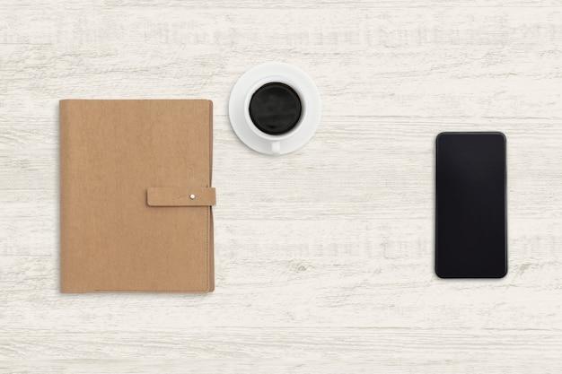 Smartphone z notatnikiem i filiżanką kawy na drewnie.