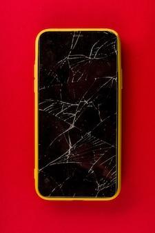 Smartphone z pękniętym ekranem na czerwonym tle