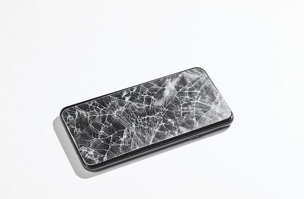 Smartphone z potłuczonym szkłem ochronnym na białym stole.