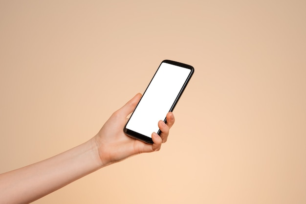 Smartphone z pustym ekranem w kobiecej dłoni na pomarańczowym tle.
