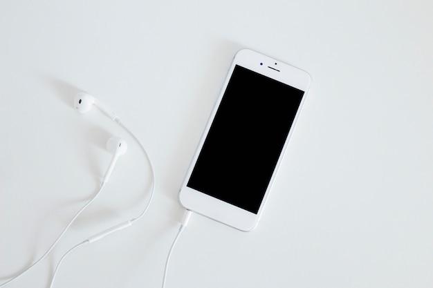 Smartphone z słuchawką odizolowywającą na białym tle