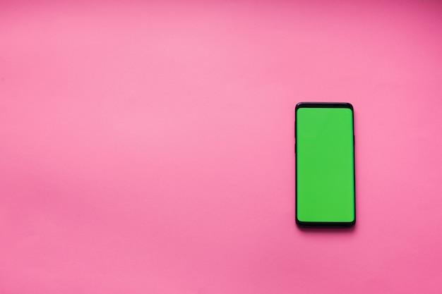 Smartphone z zielonym ekranem na różowym tle
