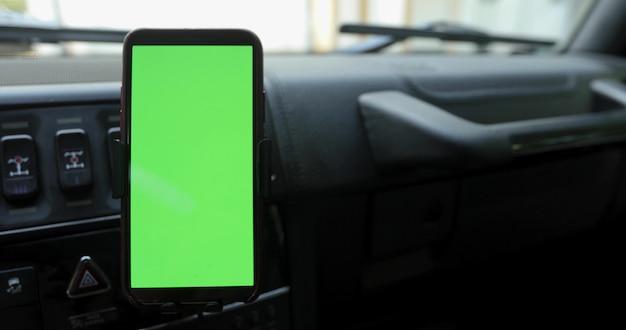 Smartphone z zielonym ekranem w uchwycie na przedniej szybie