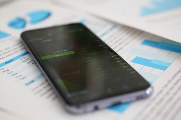Smartphone zakupu guzik i pieniężne statystyki ondisplay pastylka przy biuro stołu zbliżeniem. wewnętrzny inspektor usług kontroli sumy irs dochodzenie dochody oszczędności koncepcja pożyczki i kredytu