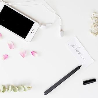 Smartphone ze słuchawkami w pobliżu tagu z tytułem, długopis, świeże płatki róż i gałązki roślin