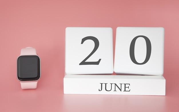 Smartwatch z kostkowym kalendarzem i datą 20 czerwca na różowym stole.