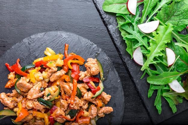Smaż mięso z warzywami w pobliżu sałatki z rukolą i rzodkiewką na kamiennych płytkach łupkowych. obiad. pyszny zdrowy lunch. widok z góry