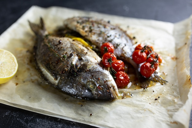 Smażąca dorado ryba na papierze z cytryną, rozmarynami i pomidorami na szarym tle, odgórny widok. grillowana ryba dorado na kamiennym talerzu.
