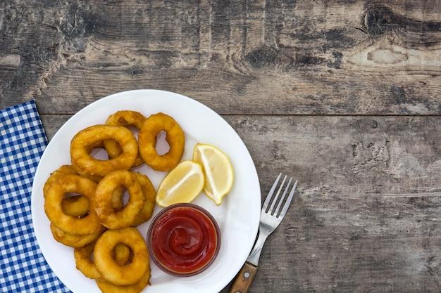 Smażący calamari dzwoni z ketchupem na drewnianej powierzchni kopii przestrzeni