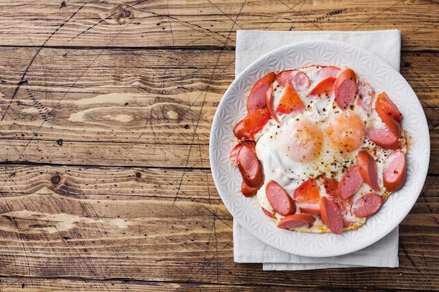 Smażący jajko kiełbasy, pomidory na talerzu na stole i.