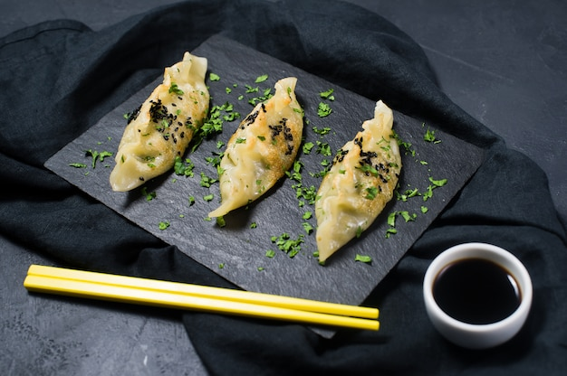 Smażący japoński gyoza na czarnej kamień desce, żółci chopsticks.