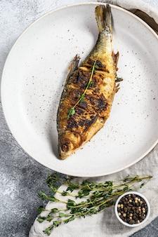 Smażący karaś na białym talerzu. ryby ekologiczne rzeczne. widok z góry