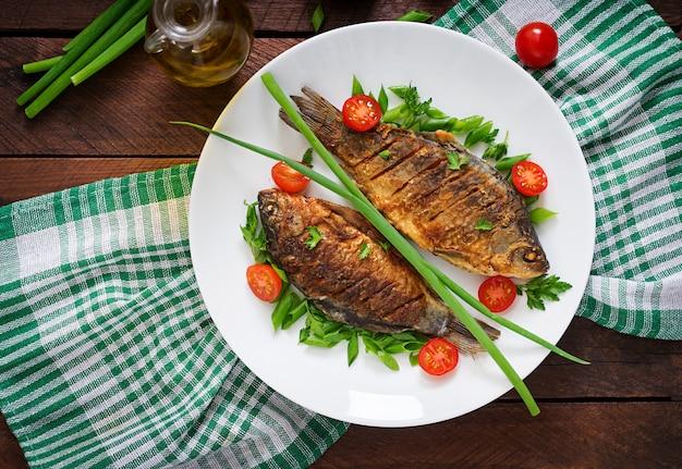 Smażący karpiowy rybi i świeża jarzynowa sałatka na drewnianym stole. leżał płasko. widok z góry