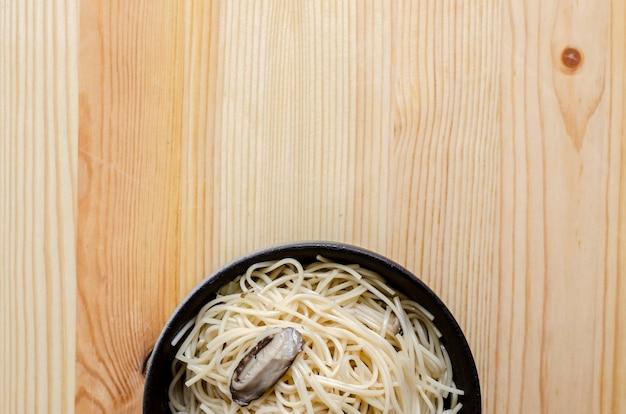 Smażący kluski w czarnym pucharze na drewnianym stole, tajlandzki uliczny jedzenie