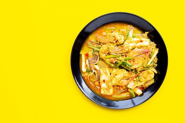Smażący owoce morza z curry'ego proszkiem na żółtym tle.