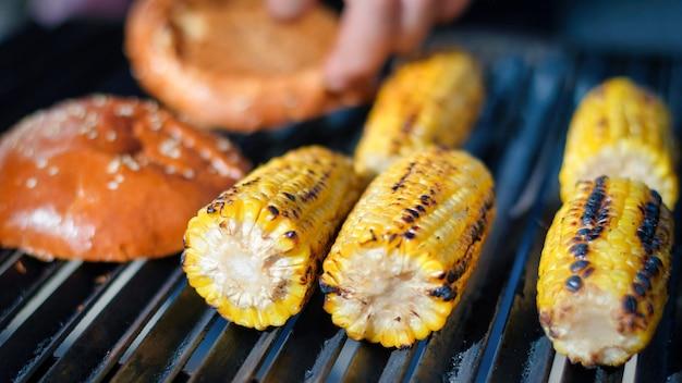 Smażenie kolb kukurydzy i bułka burger na grillu. grill