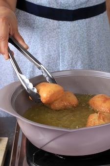 Smażenie odading (kue bantal), indonezyjskie wirusowe jedzenie uliczne, wykonane z mąki, drożdży i cukru.